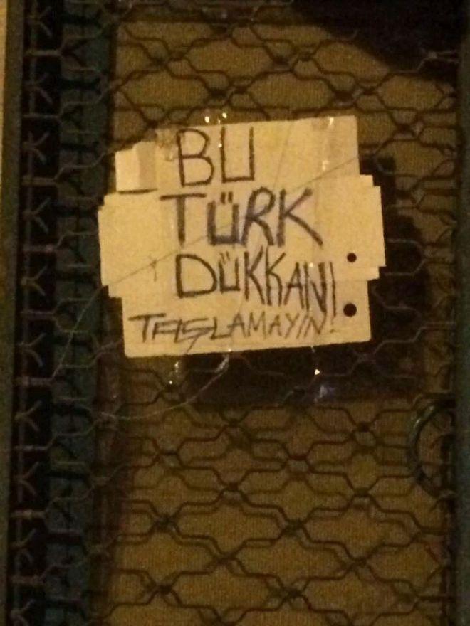 """Op het bordje staat """"Dit is een Turkse winkel - geen stenen gooien"""" Ankara gisteren. Rechts viert zijn overwinning met het ontketenen van zijn haat tegen minderheden."""