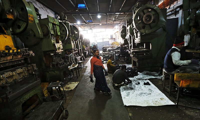 Workers make auto parts on machines inside a manufacturing unit in Faridabad