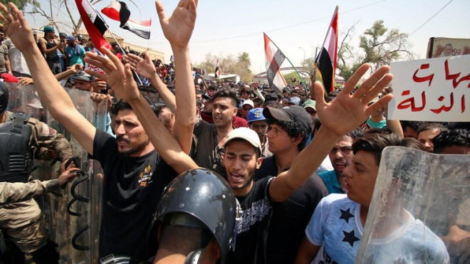 People shout slogans during a protest near the main provincial government building in Basra