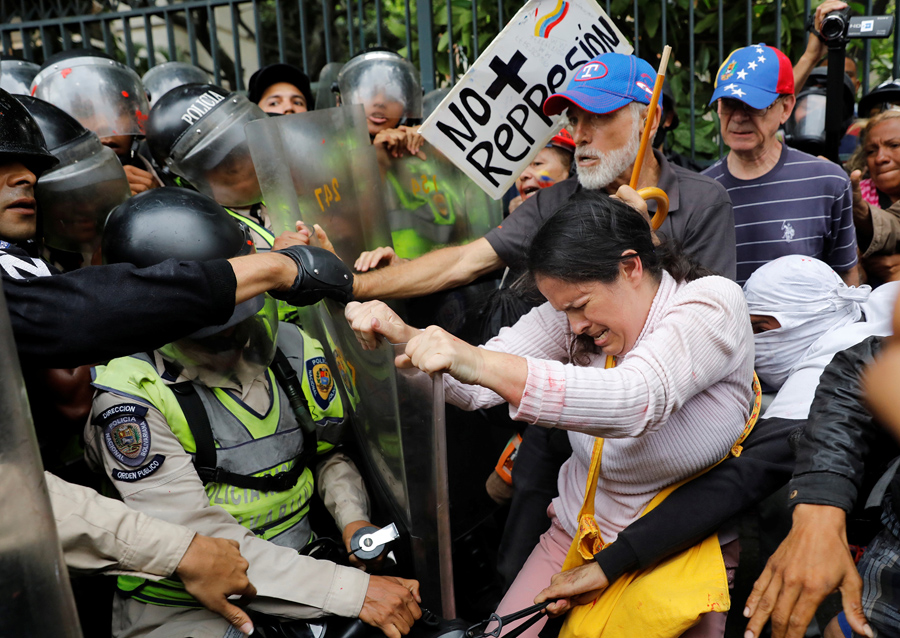 Opposition supporters confront riot security forces while rallying against President Nicolas Maduro in Caracas